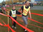 A runner who is blind and her running guide pass through the Finish gate.